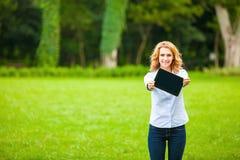 Jonge dame met tablet in park Stock Afbeeldingen