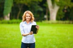 Jonge dame met tablet in park Stock Afbeelding