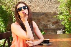 Jonge dame met zonnebril die kus op terras blazen Stock Fotografie