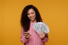 Jonge dame over blauwe achtergrond Kijkend camera die vertoning van het mobiele geld van de telefoonholding tonen stock foto
