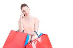 Jonge dameholding het winkelen en zakken die denken glimlachen Royalty-vrije Stock Afbeelding
