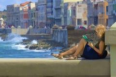 Jonge damelezing in Malecon-promenade in Havana, Caraïbisch Cuba, stock afbeeldingen