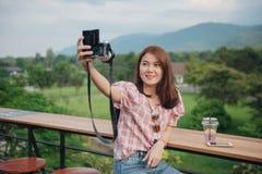 Jonge damereiziger die selfie met haar camera in in openlucht koffie met mooi aardlandschap nemen royalty-vrije stock fotografie