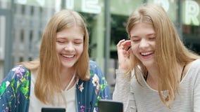 Jonge dames die hun telefoons in stad met behulp van stock fotografie