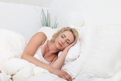 Jonge dameslaap vreedzaam in bed Stock Fotografie