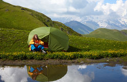 Jonge damezitting dichtbij een tent en haar watergedachtengang vooraan Royalty-vrije Stock Afbeelding
