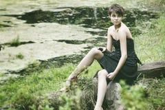 Jonge damezitting dichtbij vijver Stock Foto