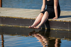 Jonge damezitting op de pier royalty-vrije stock foto's