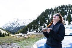 jonge damezitting op een bonnet van een auto die smartphone in de bergen met behulp van Gelukkig Meisje die bericht met zonglazen royalty-vrije stock fotografie