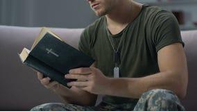 Jonge de bijbelzitting van de sergeantlezing op bank, godsdienstig geloof, harde tijdsteun stock video