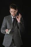 Jonge de dollarbankbiljetten van de zakenmanholding en het tonen van o.k. teken Royalty-vrije Stock Foto's