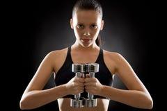 Jonge de gewichten zwarte achtergrond van de vrouwenoefening Stock Fotografie