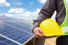 Jonge de greep gele helm van de bedrijfsmenseningenieur bij zonnepaneel stock afbeelding