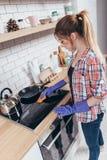 Jonge de keukenhand die van de vrouwen schoonmakende oven thuis schone van de fornuisbovenkant en brander dekking afvegen royalty-vrije stock foto