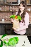 Jonge de kruidenierswinkel van de vrouwenholding het winkelen zak met groenten die zich in de keuken bevinden Stock Afbeelding