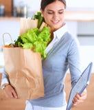 Jonge de kruidenierswinkel van de vrouwenholding het winkelen zak met groenten Status in de keuken Stock Afbeeldingen