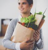 Jonge de kruidenierswinkel van de vrouwenholding het winkelen zak met groenten die zich in de keuken bevinden Royalty-vrije Stock Foto