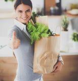 Jonge de kruidenierswinkel van de vrouwenholding het winkelen zak met groenten en het tonen van o.k. Stock Foto's