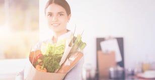 Jonge de kruidenierswinkel van de vrouwenholding het winkelen zak met groenten Status in de keuken Stock Foto