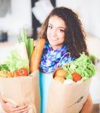 Jonge de kruidenierswinkel van de vrouwenholding het winkelen zak met groenten Status in de keuken Royalty-vrije Stock Fotografie