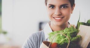 Jonge de kruidenierswinkel van de vrouwenholding het winkelen zak met groenten Status in de keuken Royalty-vrije Stock Foto's