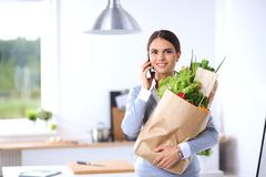Jonge de kruidenierswinkel van de vrouwenholding het winkelen zak met groenten Status in de keuken Royalty-vrije Stock Afbeelding