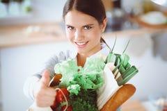 Jonge de kruidenierswinkel van de vrouwenholding het winkelen zak met groenten Status in de keuken Royalty-vrije Stock Afbeeldingen