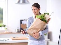 Jonge de kruidenierswinkel van de vrouwenholding het winkelen zak met groenten Status in de keuken Stock Fotografie