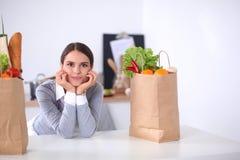 Jonge de kruidenierswinkel van de vrouwenholding het winkelen zak met groenten Status in de keuken Stock Afbeelding