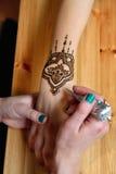 Jonge de kunstenaar van vrouwenmehendi het schilderen henna op de hand Royalty-vrije Stock Afbeeldingen