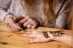 Jonge de kunstenaar van vrouwenmehendi het schilderen henna op de hand Stock Foto's