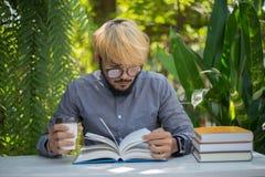 Jonge de mens van de hipsterbaard het drinken koffie terwijl het lezen van boeken in h royalty-vrije stock afbeelding