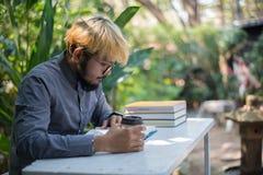 Jonge de mens van de hipsterbaard het drinken koffie terwijl het lezen van boeken in h stock foto