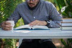 Jonge de mens van de hipsterbaard het drinken koffie terwijl het lezen van boeken in h royalty-vrije stock afbeeldingen