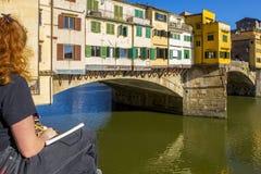 Jonge de steen middeleeuwse brug Ponte Vecchio en Arno River, Florence, Toscanië, Italië van de vrouwentekening royalty-vrije stock afbeeldingen
