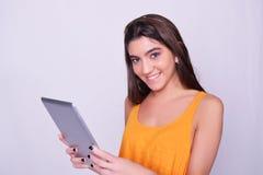Jonge de tabletcomputer van de vrouwenholding op grijze achtergrond Royalty-vrije Stock Afbeeldingen