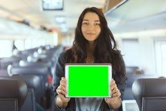 Jonge de tabletcomputer van de vrouwenholding terwijl het reizen door trein stock foto