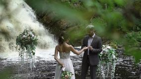 Jonge de uitwisselingsringen van het huwelijkspaar bij ceremonie dichtbij waterval stock videobeelden
