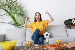 Jonge de ventilator van de vrouwensport het letten op gelijke in een geel t-shirtdoel stock fotografie