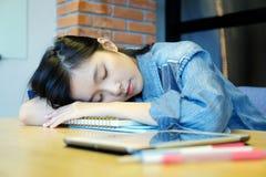 Jonge de vrouwenslaap van Azië zoals uitgeput van het werken met laptop stock fotografie