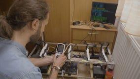Jonge deskundige ingenieur die met digitale van de cryptocurrencymijnbouw van de machtsmeter de installatieconsumptie onderzoeken stock videobeelden