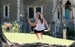 Jonge die blondevrouw op houten schommeling dichtbij oud kasteel wordt geconcentreerd Stock Afbeelding
