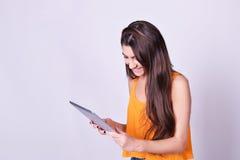 Jonge die de tabletcomputer van de vrouwenholding op grijze achtergrond wordt geïsoleerd royalty-vrije stock fotografie