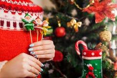 Jonge die het speelgoedkerstman van de vrouwenholding door Kerstboom thuis wordt gevormd die, de wintersweater dragen Het concept royalty-vrije stock foto