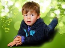 Jonge die jongen in bellen wordt omringd & bokeh Stock Afbeelding