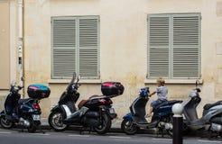 Jonge die jongensplaatsen op een motorscooter op een straat van Parijs wordt geparkeerd Stock Foto's