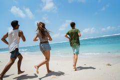 Jonge die man en vrouw aan het strand in werking wordt gesteld royalty-vrije stock afbeeldingen