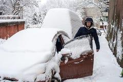 Jonge die mens dichtbij auto door sneeuw wordt behandeld royalty-vrije stock fotografie