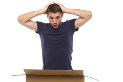 Jonge die mens het kijken aan de doos wordt verrast Op een witte achtergrond stock afbeeldingen