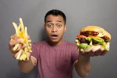 Jonge die mens met de grootte van zijn pakket van het hamburgergedeelte wordt verrast Stock Fotografie